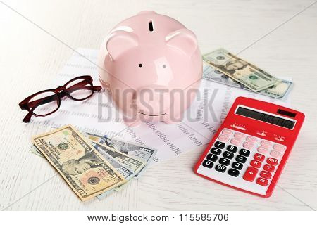 Bookkeeping concept. Piggy bank, calculator, dollars and papers on white wooden background