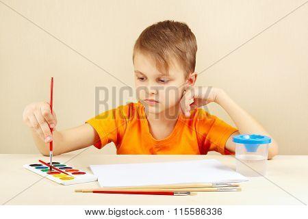 Beginner artist in orange shirt going to paint watercolors
