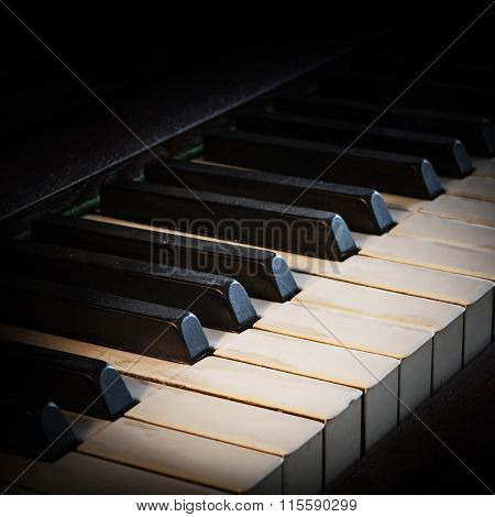 Antique Piano Keyboard Fading Into A Black Background With Copy Space
