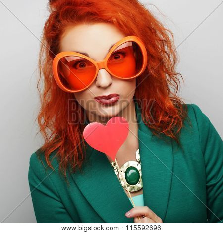 woman holding a party heart and glasses.