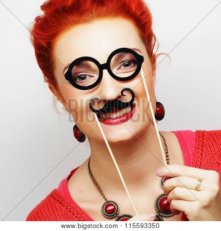 girl holding mustache and glasses on a stick.
