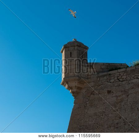 Turret Against Blue Sky Background. Castle Of Santa Barbara In Alicante City