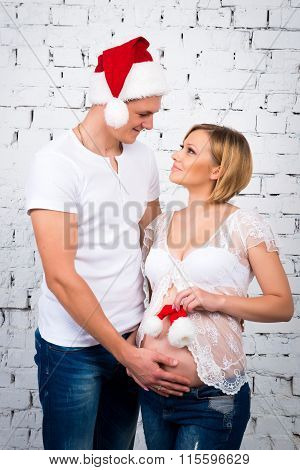Young Pregnant Couple Near A White Brick Wall With A Small Child Santa Hat