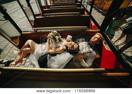 Bride and groom posing in a tour car