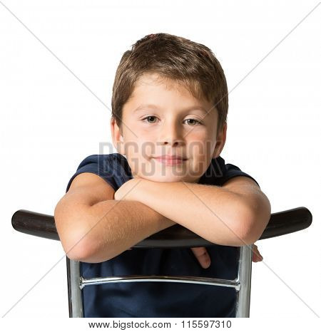 Picture taken on a white background. Very beautiful seven year old boy sits astride a chair