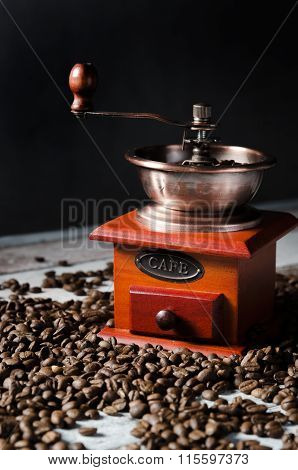 Old Retro Coffee Grinder On Wooden Background With Coffee Beans