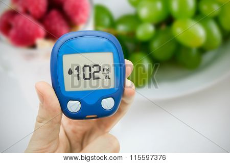 Diabetes Doing Glucose Level Test. Fruits In Background
