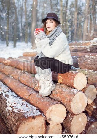 Beautiful young  woman holding hot drink wearing knitted scarf, fedora hat and winter boots covered with snow flakes. Sitting on pile of pine logs. Snowing winter fashion concept.
