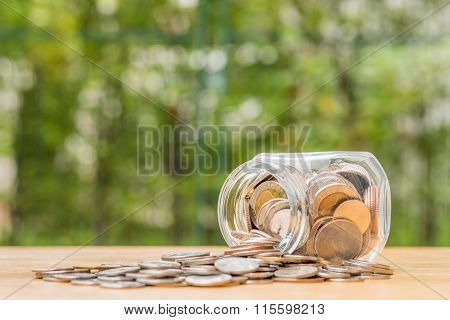 Thai Baht Coins Spilling Out Of Money Jar