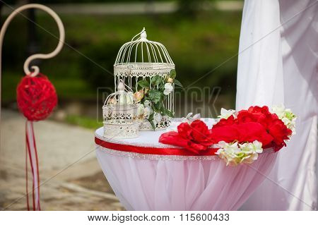 Romantic Valentyne Wedding Aisle Red Decorations And Flowers And A White Engraved Cage Closeup