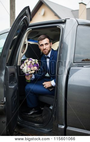 Happy Handsome Groom With A Beard, Getting Out Of Wedding Car Holding A Bouquet