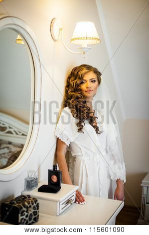 Sexy Blonde Bride In White Robe Posing Near A Mirror While Preparing For The Wedding Ceremony