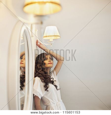 Sexy  Bride In White Robe Posing Near A Mirror While Preparing For The Wedding Ceremony