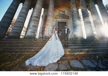 Panoramic View Of A Fairytale Newlywed Couple Holding Hands In Front Of Old Baroque Ghotic Church Wi