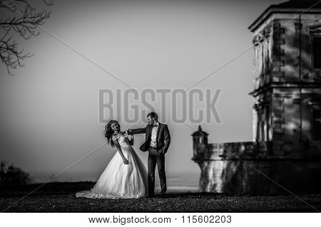 Sensual Happy Couple Posing And Hugging Near Old Castle At Sunset With A Beautiful Skyline Backgroun