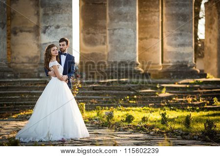 Sensual Romantic Newlywed Bride And Groom Hugging In Front Of Old Baroque Church With Columns At Sun