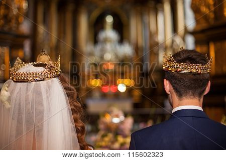 Fairytale Couple, Bride And Groom In Crowns During Wedding Ceremony In Church