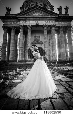 Panoramic View Of A Fairytale Newlywed Couple Hugging And Kissing In Front Of Old Baroque Ghotic Chu