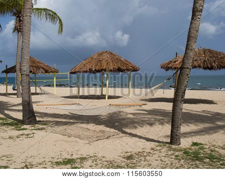 Hammock, Tiki Huts, And Volleyball Net On The Beach