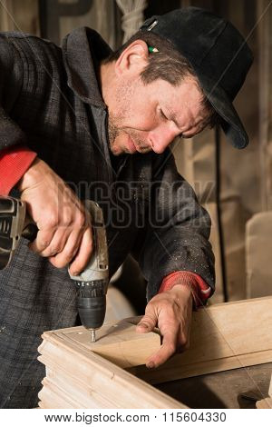 Carpenter drills a hole in the wooden products in the carpentry workshop.