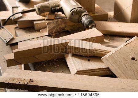 Billets of wood for furniture lie on a workbench in a carpentry workshop.