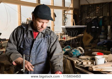 Joiner works with wood in the carpentry workshop.