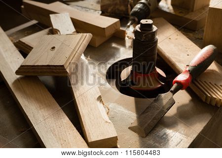 Wood products and tools lie on a workbench in a carpentry workshop.