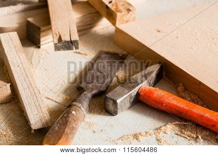 Hammer and chisel  lie on a workbench among scraps of wood