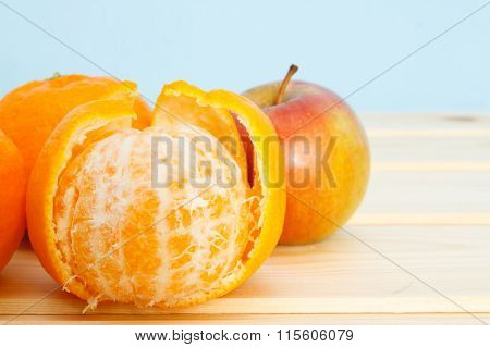 Mandarins And Apple On Wooden Table