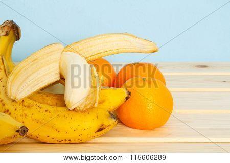 Bananas, Mandarines On Wooden Table