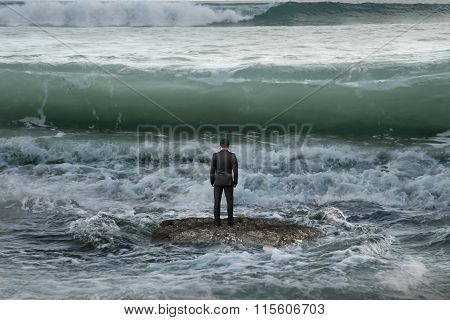 Businessman Standing On Rock In The Ocean Facing Oncoming Waves