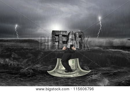 Businessman Carrying Structure Of Fear On Money Boat With Storm