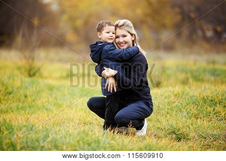 Young mother and son in autumn forest park, yellow foliage. Casual wear. Kid wearing blue jacket. In