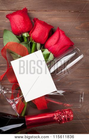 Valentines day greeting card, champagne and red roses on wooden table. Top view with copy space