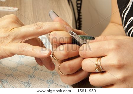 Woman getting nail manicure. Woman in a nail salon receiving a manicure by a beautician