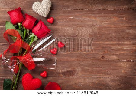 Red roses, hearts and champagne glasses over wood with copy space. Valentines day background