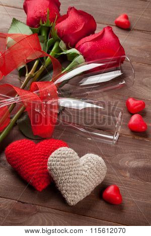 Red roses, hearts and champagne glasses over wood. Valentines day concept