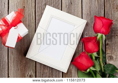 Photo frame, red roses and Valentines day gift box over wooden table. Top view with copy space