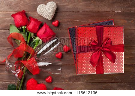 Valentines day gift box and red roses on wooden table. Top view