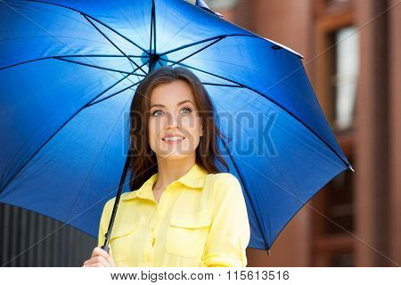 Beautiful young woman in yellow shirt with blue umbrella in city center.