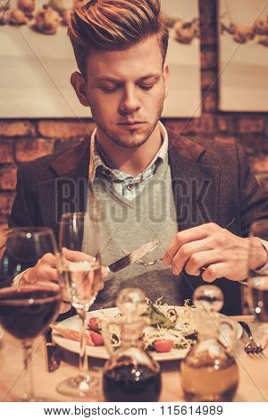 Stylish wealthy man eating at restaurant.