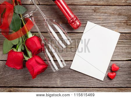Red roses with Valentines day greeting card and champagne over wooden background. Top view with copy space