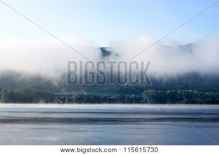 Early Morning Fog At A Blue Lake With Mountains In The Background