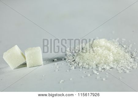 Sugar Cubes And White Granulated Sugar On Isolated White Background