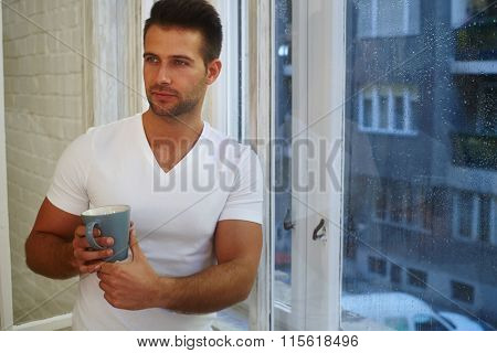 Daydreaming young man standing front of window in rainy morning, holding mug of tea.