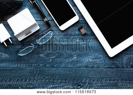 Dramatic and Dark Light Filtered Office desktop with a lot of objects including a smartphone, a tablet, a mouse, eyeglasses, a dock and more.