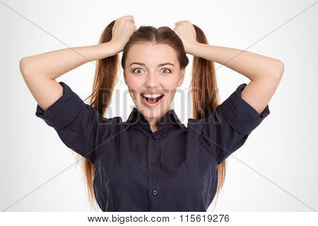 Funny excited young woman with two ponytails holded by hands over white background