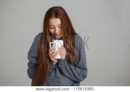 Beautiful smiling young woman feeling cold and drinking hot tea over grey background