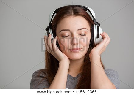Pretty inspired young woman with long hair listening to music with eyes closed over grey background