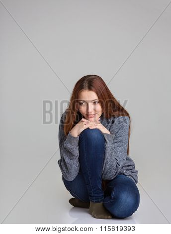 Full length portrait of happy pensive young woman in grey sweatshirt and jeans sitting and thinking over grey background
